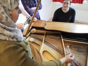 Bild von Ahmed Hussien mit Schulkolleginnen am Klavier
